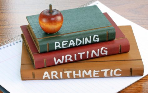 Three wooden books with Reading, Writing and Arithmetic painted on them sitting on a sprital notepad.